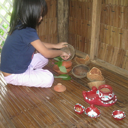 Cooking with clay pots, dried coconut shells, and leaves and flowers